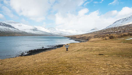Women journey in the east fjord of Iceland with beautiful mountains range.