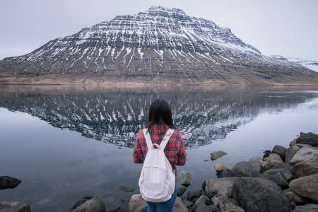 Portrait of Asian girl travel and standing in front of Hólmatindur an iconic mountain in Eskifjörður town of east Iceland.