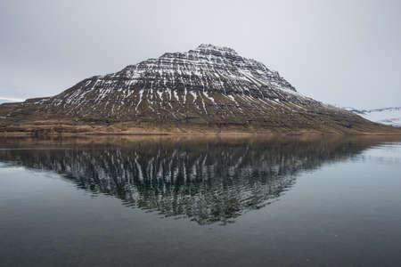 The reflection of Holmatindur mountain of Eskifjordur town of east Iceland.