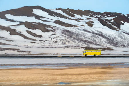 A yellow local bus driving on the road with the beautiful landscape in Myvatn region of Northern Iceland.