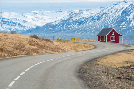 A small red cottage located in east fjord of Iceland with the country road a part of the main Ring road passed this east region of the country.