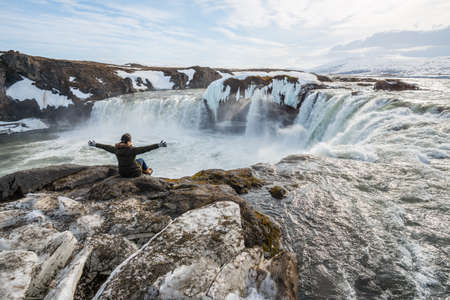Asian tourist sitting on the edge of the cliff in front of Godafoss (Goðafoss) the waterfall of god one of tourist attraction place in northern region of Iceland.
