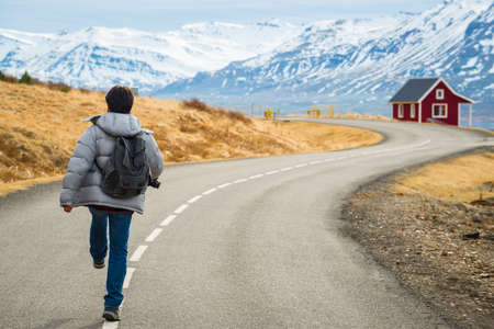 Asian man walking on the empty road in the countryside of Iceland.