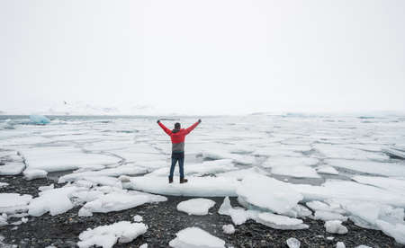 A man standing on the ice floating in Jokulsarlon glacier lagoon in the cloudy day of Iceland. Stok Fotoğraf