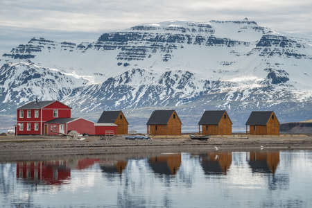 Beautiful scenery and reflection of the small cottage in Mjoeyri resort nearly Eskifjordur town of east fjord of Iceland.