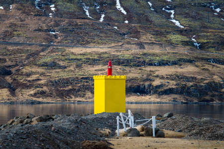 The small yellow light house at the fjord of Eskifjordur town of east Iceland. Stok Fotoğraf