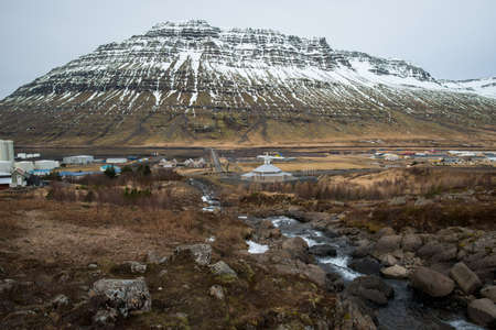 Scenery view of Eskifjordur town in East region of Iceland with the mighty mountain named Holmatindur at the background. Imagens