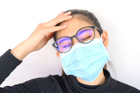 Young Asian woman feel headache and wearing medical mask for protect bad air pollution. Air pollution has been associated with diseases of the heart and lungs, cancers and other health problems.