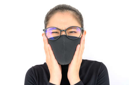 Close up of young Asian woman coughing and wearing black mask for protect bad air pollution. Air pollution has been associated with diseases of the heart and lungs, cancers and other health problems. Zdjęcie Seryjne