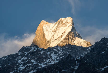 The upper summit of Machhapuchhre mountain (Mt.Fish tail) at sunset. This peak is holy mountains in Hindu religion believed it the rest place of God Shiva view from Dovan village, Nepal.