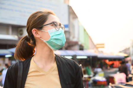 Woman wearing surgical mask for protect bad air pollution or virus in pandemic situations. Conceptual of urban lifestyle and using mask for avoid bad environment.