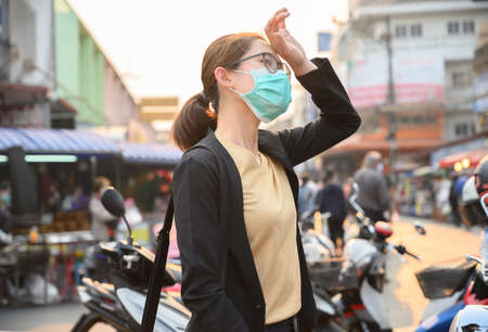 Woman having headache and wearing surgical mask for protect bad air pollution or virus. Headache maybe occurs from stress, tension or migraine etc.