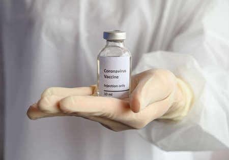 Close up of scientist doctor hand holding a sample test bottle of Covid-19 vaccine. Vaccination is one of the most effective ways to prevent diseases and helps the body's immune system from virus.