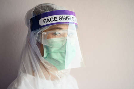 Nurse wearing PPE suit, Face shield and surgical mask for protect coronavirus disease. PPE while protecting healthcare workers from exposure to the COVID-19 virus in healthcare settings.
