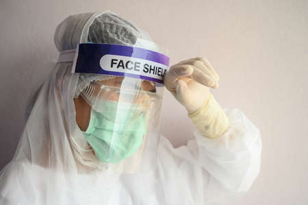 Nurse having headache and tired while wearing PPE suit for protect coronavirus disease. PPE while protecting healthcare workers from exposure to the COVID-19 virus in healthcare settings.