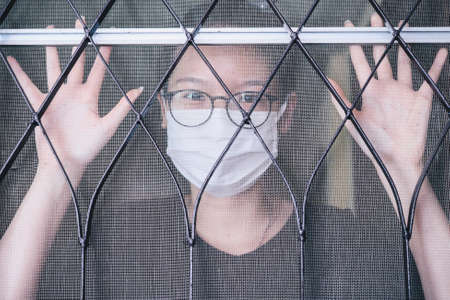 Portrait of young Asian woman wearing mask and quarantine herself in her home in covid-19 pandemic outbreak. Quarantine is used to keep someone who might have been exposed to COVID-19 away from others