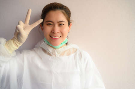 Asian Nurse wearing PPE suit and showing V sign (Victory sign). In coronavirus pandemic outbreak we should support and encourage healthcare worker by stay home and listen to medical advice.