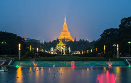 The Shwedagon pagoda with the colourful fountain view from people's park in Yangon township of Myanmar at night. It's Burma's most important Buddhist pilgrimage site. 新闻类图片