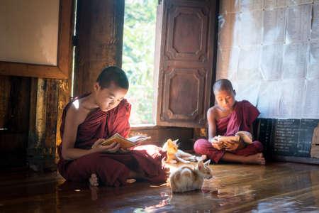 NYAUNGSHWE, MYANMAR - OCT 05 2014: Myanmar novice reading the book in the Shwe Yaunghwe Kyaung monastery the big window temple in Myanmar.