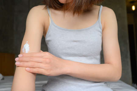 Cropped shot of woman applying lotion (or moisturizer) on her skin for softening the skin. Some skincare products available in multiple formats, such as lotions, gels, creams etc.