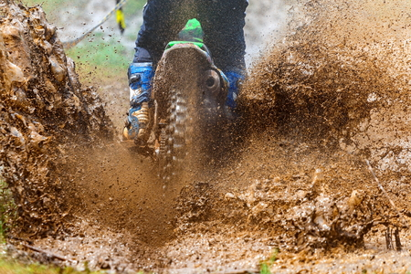 enduro rijdt door de modder met grote plons, de bestuurder spettert modder op nat en modderig terrein, motocrossracer op een nat en modderig terrein dat de bestuurder volledig bedekt.
