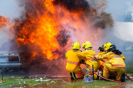fireman using water and extinguisher car is on fire,Firefighter using extinguisher and water from hose for fire fighting,burning car Gas,Rescue Equipment.