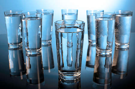 Eight glasses of water backlit in blue with selective focus on the front glass Reklamní fotografie - 26543133