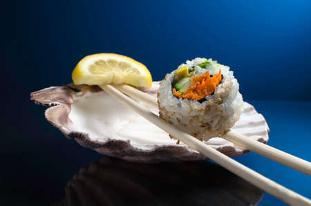 california roll: A piece of California Roll sushi on a pair of chopsticks with sea shell background  Stock Photo