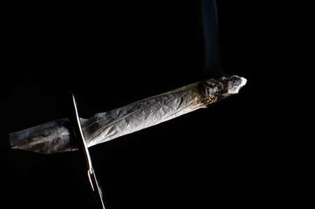 Pain Management: A smoldering marijuana joint with black background  Stock Photo