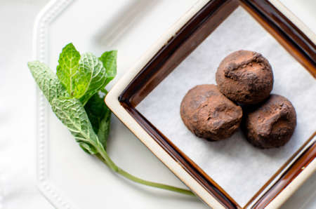 Small plate of three chocolate truffles on white plates