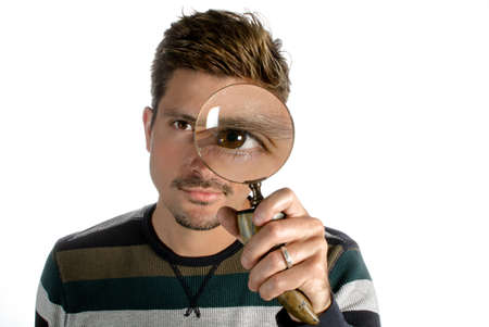 A man looking through a magnifying glass with an eye enlarged  photo