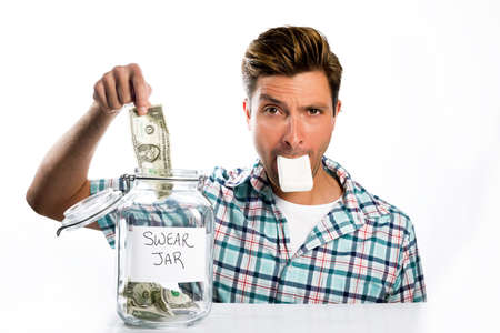 A man paying into a swear jar with a bar of soap in his mouth