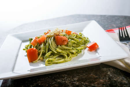 Fettucini pasta with pesto sauce and fresh tomatoes