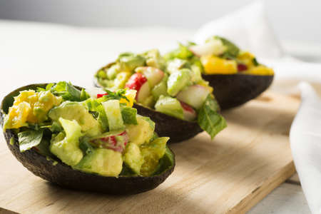 eating salad: Avocado radish and citrus salad in avocado skins Stock Photo