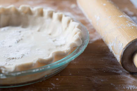 Fresh rolled pie crust in a pie plate baking Stock Photo