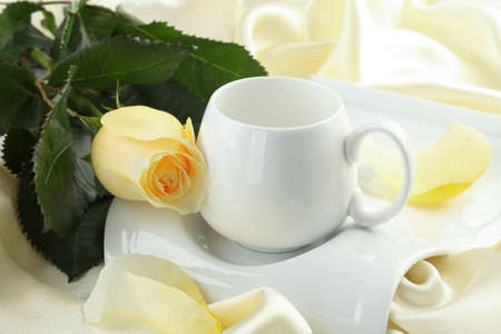 roze: A cup on a white platter with a yellow rose