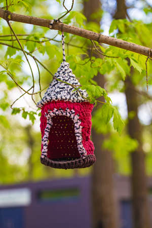 knitted from yarns birdhouse hanging in the park