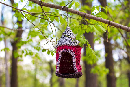 estate: knitted from yarns birdhouse hanging in the park