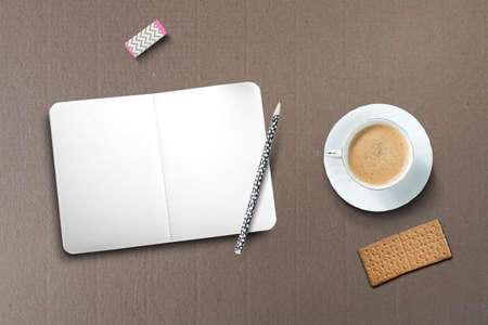 uncluttered: Composition with a cup of coffee, biscuits and an empty notebook