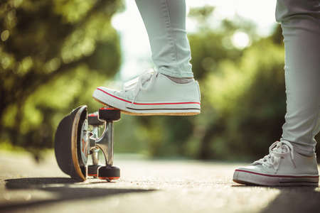 skate park: Female feet in white sneakers and skateboard close up