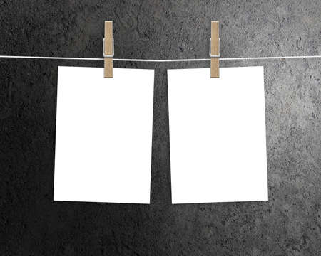 paper sheet: Paper cards hanging on a clothesline with clothespins on dark background