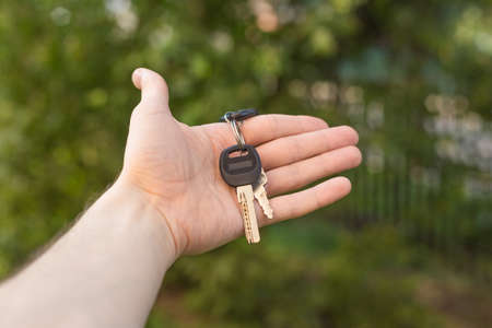 the guy holds the keys in hand close up