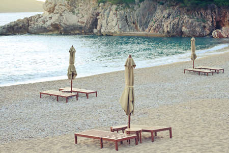 Beautiful sea view with rocks, sunbeds and umbrellas photo