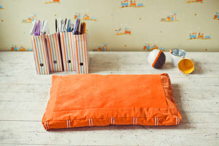 matress: Orange pet mattress with colourful boxes and pails on the floor