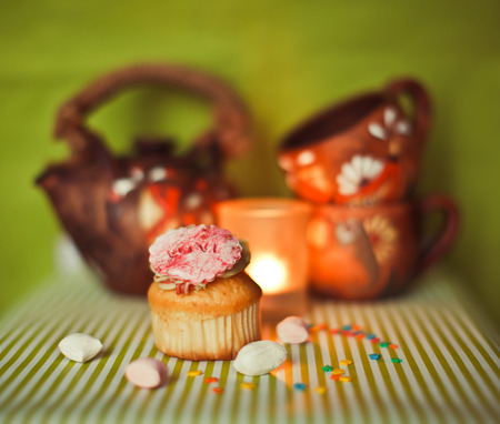 cake pick: Cupcake on green white background with candies, tea pot and cups Stock Photo