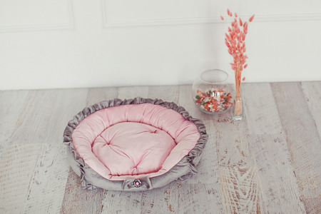Pink and gray pet mattress with flowers in interior photo