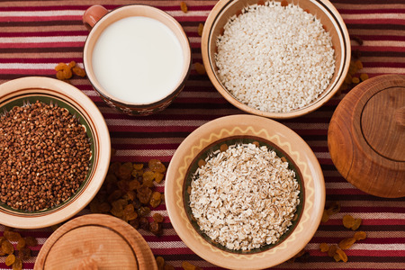 Photo of buckwheat, oat flakes, rice and milk in plates photo