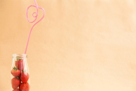 drinking straw: Sweet strawberries in the bottle with drinking straw on brown background