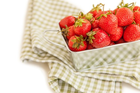 Fresh strawberry in a metal box isolated on white background photo