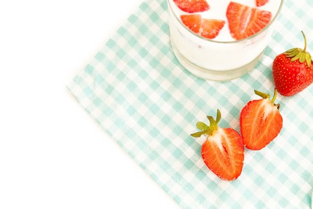 harvest background: Summer harvest background: tasty ripe strawberries and cup of fresh milk on a tablecloth isolated on white